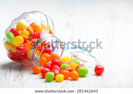 Colorful candies in jar on wooden background - stock photo