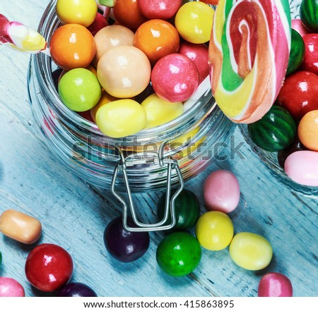 Colorful candies in jar on wooden background. focus on sweets and a glass jar
