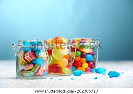 Colorful candies in jars on table on blue background background - stock photo