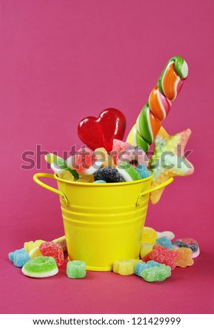 Colorful candies in yellow bucket on pink background.