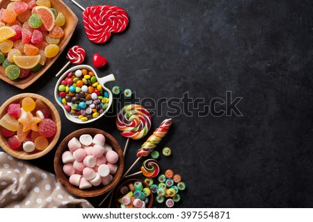 Colorful candies, jelly and marmalade on stone background. Top view with copy space - stock photo