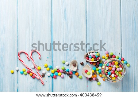 Colorful candies on wooden background. Top view with copy space - stock photo