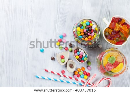 Colorful candies on wooden table background. Top view with copy space - stock photo