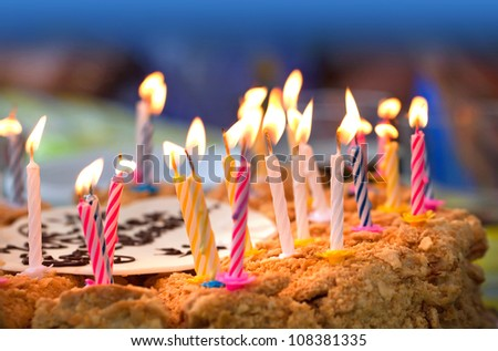Colorful candles on  birthday cake above dark background - stock photo