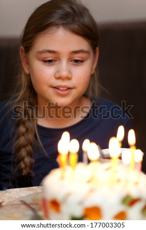 Colorful candles on birthday jelly cake in the dark. Selective focus - stock photo