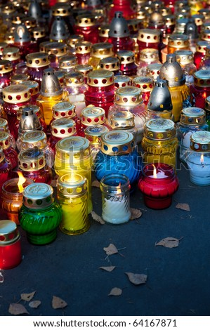 Colorful candles on cemetery during Halloween holiday - stock photo