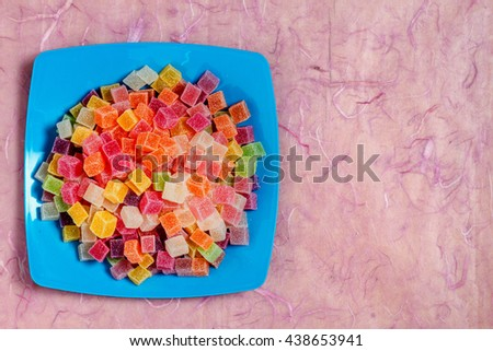 Colorful candy and jelly in color dish on pink background - stock photo