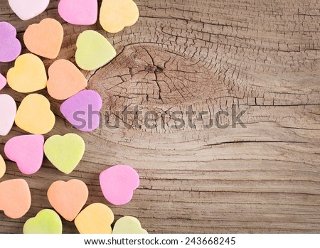 Colorful candy hearts on wooden background - stock photo