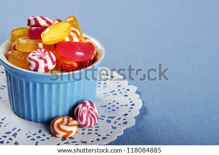 Colorful candy in a blue ceramic bowl closeup - stock photo