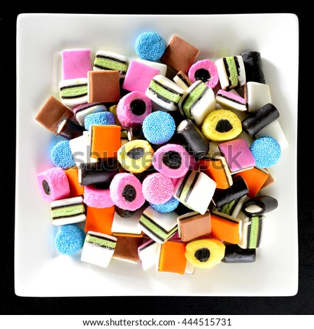 Colorful candy in plain white dish. Liquorice allsorts in many colors and shapes. Filter effects.
