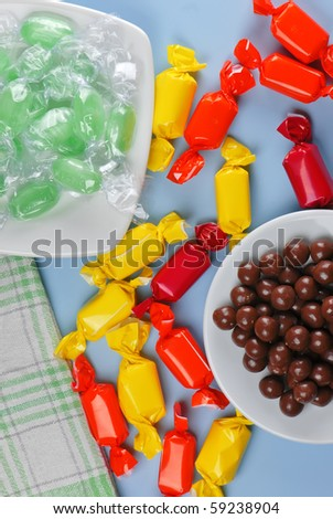 Colorful candy`s, different shapes on blue table - stock photo