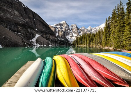 Colorful canoes lined up at lakeside. Moraine Lake, Banff National Park, Alberta, Canada - stock photo