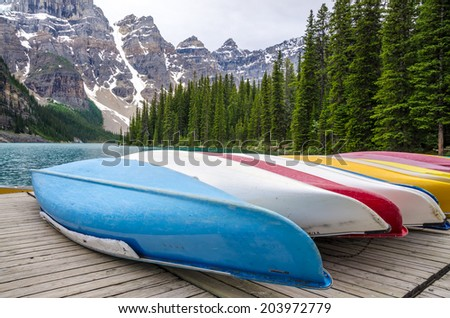 Colorful Canoes resting on the dock at Moraine lake in Banff National Park, Alberta, Canada - stock photo