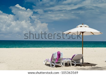 Colorful canvas beds on the beach with beautiful blue sky - stock photo