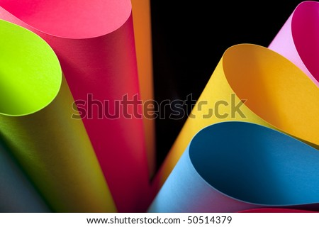 Colorful card stock in unique elliptical shapes with shadow effect and selective focus on a black background. - stock photo