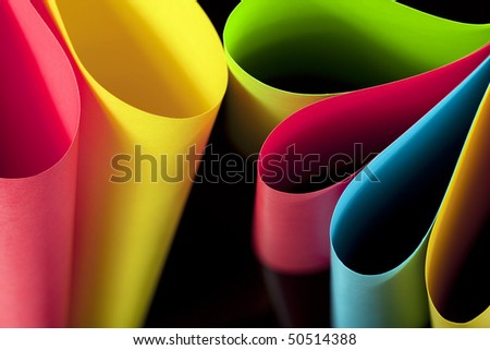 Colorful card stock in unique elliptical shapes with shadow effect and selective focus on a black background.