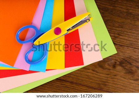 Colorful cardboard and scissors on table close-up - stock photo