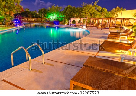Colorful caribbean swimming pool at the evening (night) time  in mexican resort . - stock photo