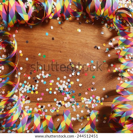 Colorful carnival frame over a wooden background with streamers and confetti with central copyspace - stock photo