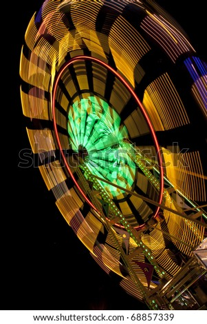 Colorful carnival ride with motion blur from State or County Fair - stock photo