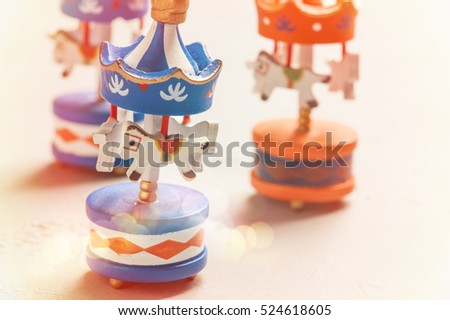 Colorful carousels wooden toys on concrete background. Place for text, baby shower or celebration concept. Toned image