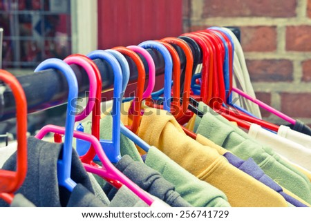 Colorful casual sweaters and hoodies hanging on a rack