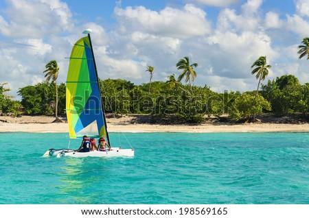 Colorful catamaran on azure water against azure water  - stock photo