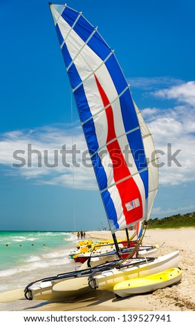 Colorful catamaran with its sails painted in bright colors on the beach of Varadero in Cuba