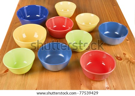 Colorful  ceramic blue, red, yellow, green, meal, bowls on wooden table.