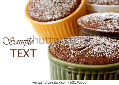 Colorful ceramic ramekins with freshly baked gingerbread sprinkled with powdered sugar.  Macro with shallow dof. - stock photo