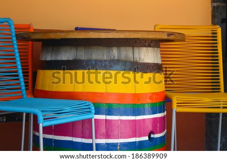 Colorful chairs and barrel table on mexican plaza - stock photo