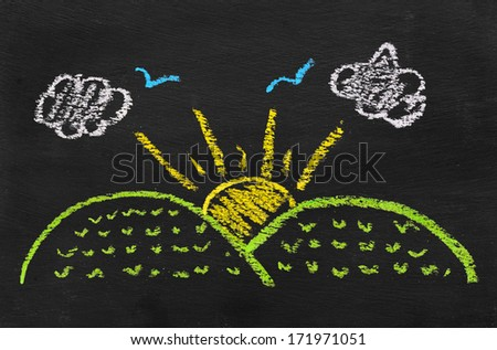 Colorful chalk illustration of sun rise by kid on blackboard  - stock photo