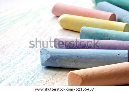 Colorful chalk on white paper with scribbles.  Macro with shallow dof and copy space. - stock photo