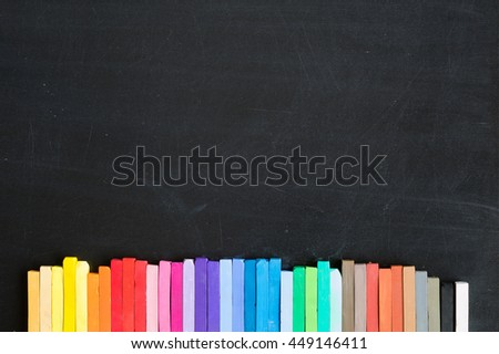 Colorful chalks and soft pastels lined up on blackboard background banner