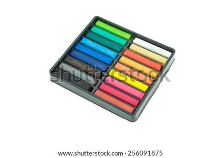 Colorful chalks in a variety of colors arranged in tray on a white background - stock photo