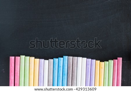 Colorful chalks lined up on school blackboard background
