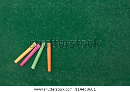 Colorful chalks on grungy green chalkboard texture