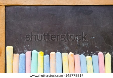 Colorful chalks on old empty blackboard - stock photo