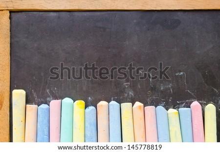 Colorful chalks on old empty blackboard - stock photo