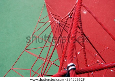 Colorful children playground made of ropes to climb. Red and green color. - stock photo