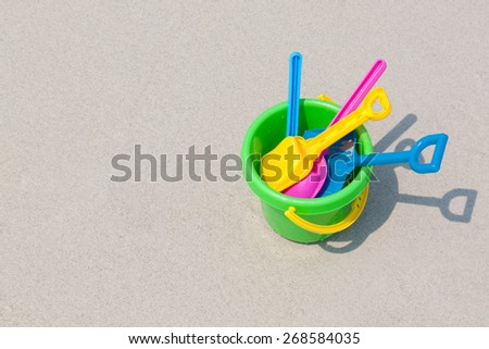 Colorful Children's beach toys on sand - stock photo