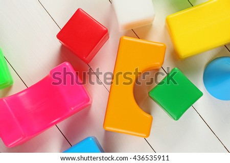 Colorful  children's building blocks on white wooden background - stock photo