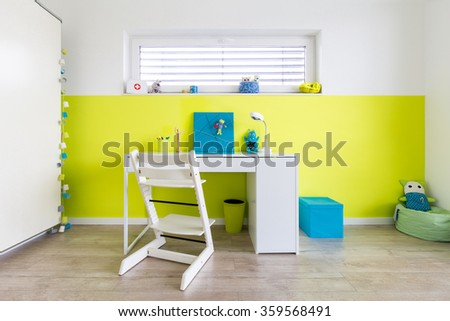 Colorful Children's Playroom with Desk and a green wall - stock photo