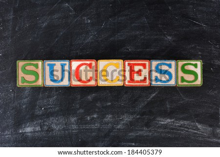 Colorful childrens blocks spelling out Success on a chalk board. Horizontal format. - stock photo