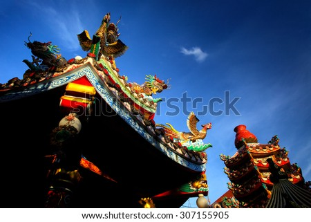 Colorful chinese buddhist temple with blue sky in Thailand. - stock photo