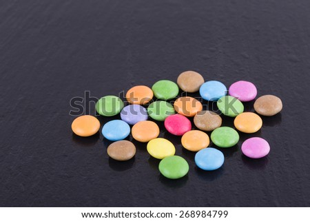 Colorful Chocolate Coated Candies on a Dark Background. Copy Space. - stock photo