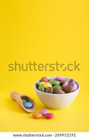 Colorful Chocolate Coated Candies on a Yellow Background.  - stock photo