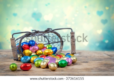 Colorful chocolate easter eggs in a basket on blue background - stock photo