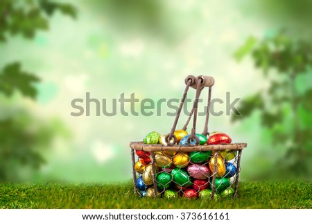 Colorful chocolate easter eggs in a basket outside in garden - stock photo