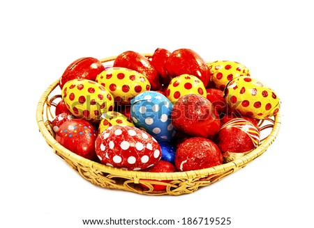 Colorful chocolate Easter eggs in basket. Isolated on white background